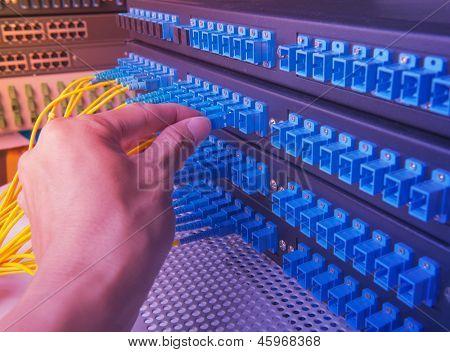Mann arbeitet im Netzwerk Serverraum mit Faser-Optik-Hub für digitale Kommunikation und internet