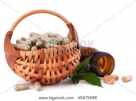 Herbal drug capsules in wicker basket isolated on white background cutout. Alternative medicine concept.