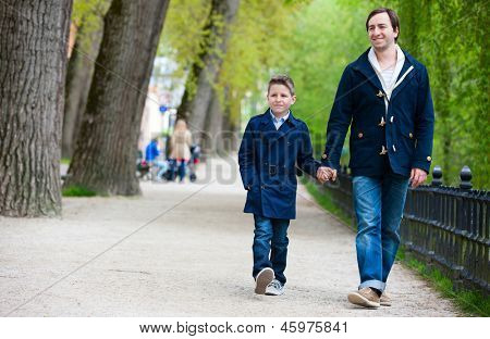 Father and son walking together in a park at spring day