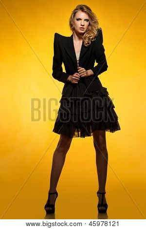 Beautiful young girl in black jacket and skirt isolated on white background