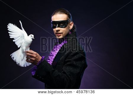 Young handsome brunette magician man in stage costume with his trained white dove