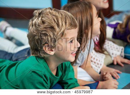 Happy little boy with female friends lying on floor in kindergarten
