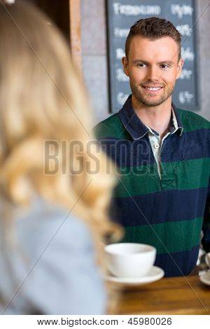 Handsome bartender serving coffee to woman at cafe
