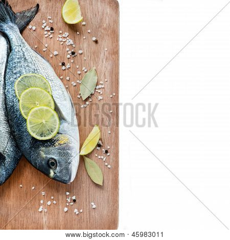 Fresh dorada fish with sea salt lime and bay leaf over wooden background
