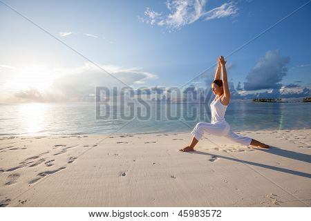 Mujer caucásica de practicar Yoga en la orilla del mar