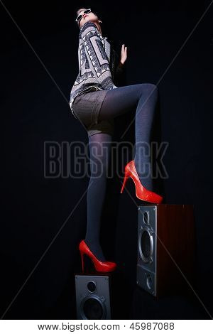 Stylish Woman Standing On A Musical Speakers