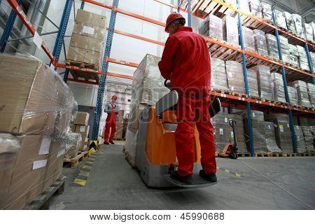 dois trabalhadores de logística - entrega de mercadorias - trabalhando no armazém com carregador de empilhadeira