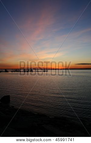 Sunset Over Water with Clouds, Pilings, and a Rocky Coastline