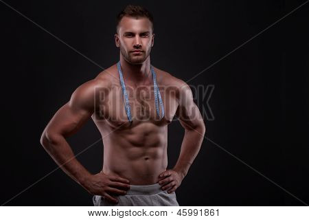 Muscular man with measurement tape