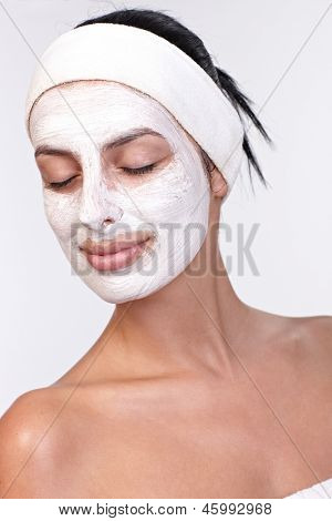 Young woman smiling with facial mask on, eyes closed, over white background.
