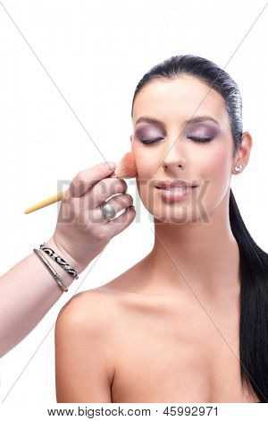 Beautiful female model with bare shoulders having makeup applied by makeup artist.