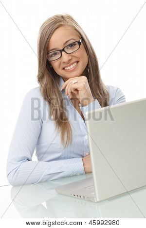 Portrait of happy young businesswoman sitting at desk with laptop computer.