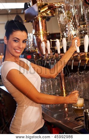 Portrait of attractive female bartender tapping mug of beer in pub, smiling.