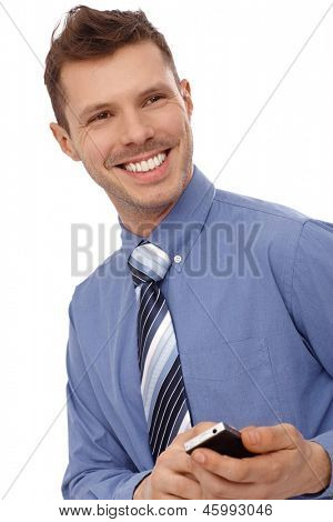 Happy young man using cellphone, texting, smiling.