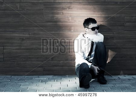 Young business man in depression sitting on the sidewalk