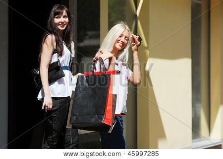 Two happy young women shopping