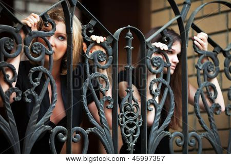 Two sad young women clinging on a the fence