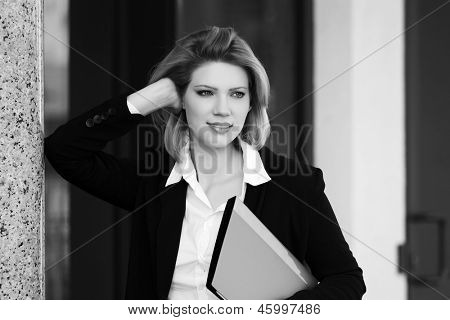 Young business woman with a folder against office windows
