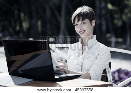 Young business woman with laptop at sidewalk cafe