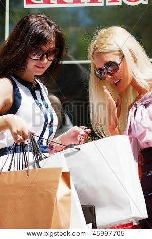 Two young women looking at shopping bags
