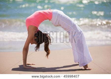Cute girl doing yoga at the beach