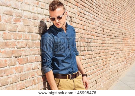 casual young man standing next to a brick wall and looking down to his side, away from the camera