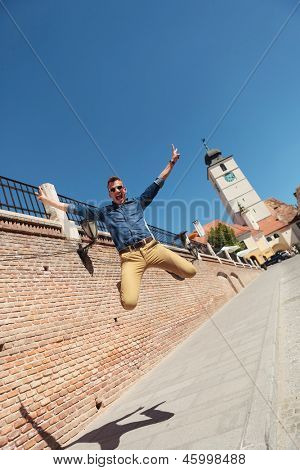 casual young man jumping in the air in the city of Sibiu, Romania