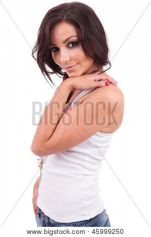 side view of a casual young woman posing with a hand in pocket and the other on her shoulder while innocently looking at the camera. on white background