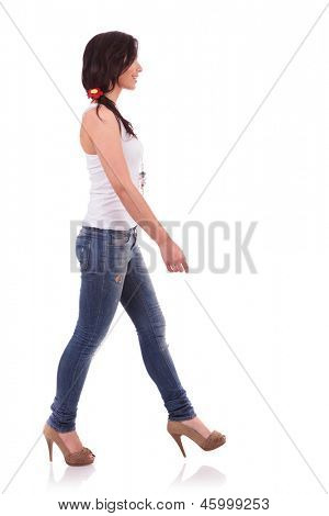 side view of a casual young woman walking ahead and looking away. on white background