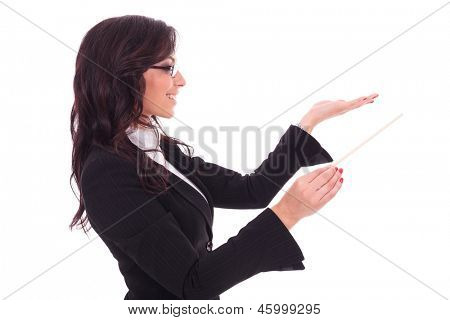side view of a young business woman holding a conductor's stick and conducting while looking away from the camera and smiling. on white background