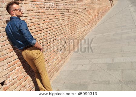 back view of a casual young man standing next to a brick wall with his hands in his pockets and looking to his side