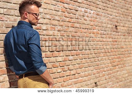 back view of a casual young man looking down with his hands in his pockets