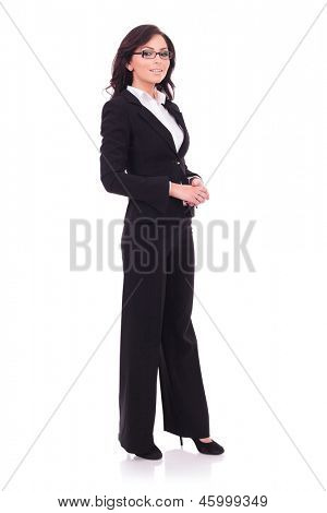 full length picture of a young business woman standing with her hands together and smiling to the camera. on white background