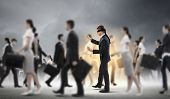 foto of blindfolded man  - Image of businessman in blindfold walking among group of people - JPG
