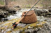 stock photo of fly rod  - Fly rod and fishing creel sitting on a large rock by a fast moving stream
