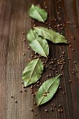 stock photo of bay leaf  - Bay leaves and mustard seeds on wooden background - JPG