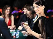 stock photo of gambler  - Poker players sitting around a table at a casino - JPG