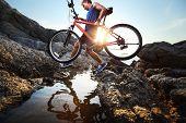 stock photo of passed out  - Young athlete crossing rocky terrain with bicycle in his hands - JPG