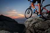 stock photo of riding-crop  - Bicycle rider standing on a rock at sunset - JPG
