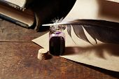 foto of inkpot  - Vintage still life with inkpot and feather near scroll and books - JPG
