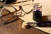 picture of inkpot  - Vintage still life with inkpot and pen near scroll on wooden table - JPG