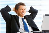stock photo of exaltation  - Happy smiling businessman working with laptop in the office - JPG