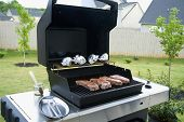 stock photo of ribeye steak  - gas grill with open lid and rib eye steaks - JPG