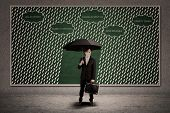 image of interrupter  - Businessman holding umbrella to protect him from rain  - JPG