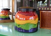 stock photo of glass-wool  - Original centerpiece of hand dyed colorful wool yarn in glass jar on table - JPG