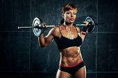 foto of human muscle  - Young sports woman with barbell - JPG