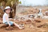 foto of booby  - Little girl on Galapagos North Seymour island with a blue footed booby on background - JPG