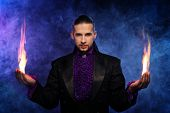 pic of wizard  - Young brunette magician in stage costume performing flame tricks - JPG