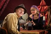 image of palm-reading  - Excited Caucasian man with grinning crystal ball reading lady - JPG