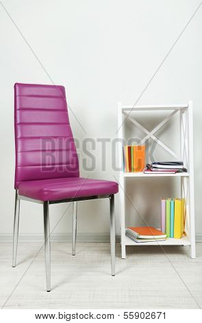 Beautiful interior with modern  color chair,  books on wooden stand, on wall background